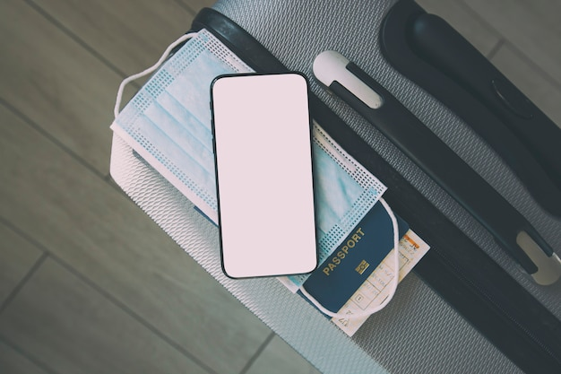 Das handy mit leerem bildschirm für digitale impfbescheinigung und reisepass, maske und ticket auf dem koffer