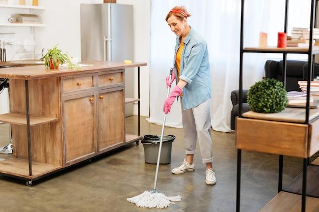 Das haus putzen. konzentrierte positive frau im häuslichen outfit, die während einer massiven reinigungssitzung den boden mit mopp wäscht