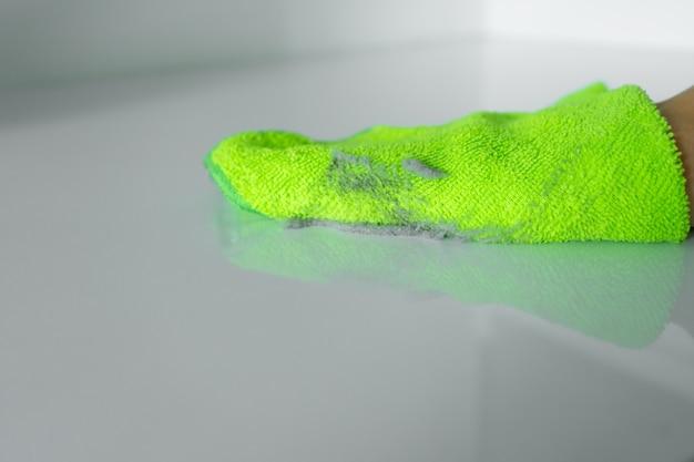 Das haus putzen. wischen sie den staub mit einem grünen lappen von einer schmutzigen oberfläche ab. viel staub auf einem lappen.