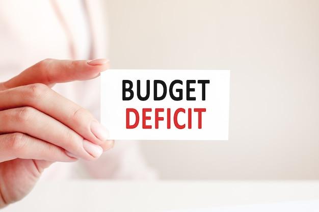 Das haushaltsdefizit wird auf eine weiße visitenkarte in der hand einer frau geschrieben.