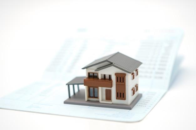 Das hausmodell ist auf banknoten platziert. in immobilien investieren
