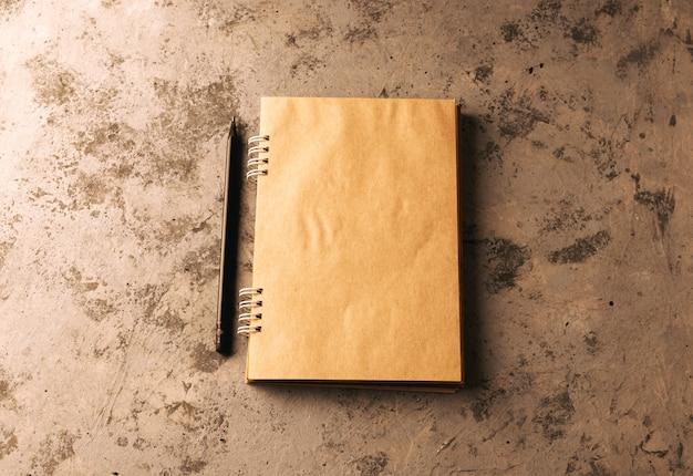 Das heft liegt in offener form auf dem tisch. layout zum schreiben von text. spiralblock in bastelpapier.
