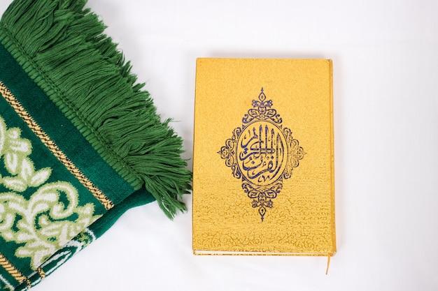Das heilige buch al quran und gebetsteppich isoliert auf weißem hintergrund