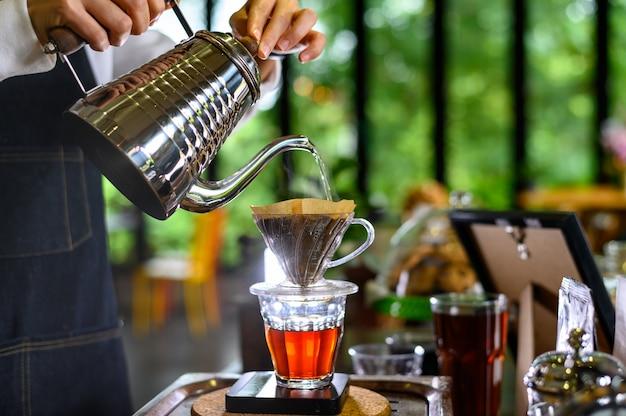 Das heiße wasser des barista-frauenmädchens bereitet gefilterten kaffee zu