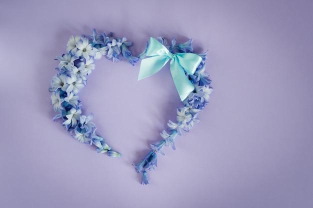 Das herz, das von den hyazinthenblüten und vom tadellosen bogen auf purpurrotem hintergrund gemacht wird.