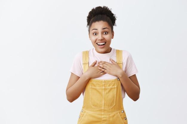 Das herz schmilzt vor erstaunlicher überraschung. berührte und überraschte gut aussehende afroamerikanerin in gelben overalls, berührte die brust und lächelte vor aufregung, beeindruckt von guter tat
