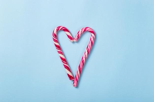 Das herz von zwei weihnachtsrot-weißen süßigkeitsstöcken auf einem hellen blauen hintergrund. draufsicht, flach zu legen