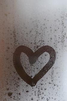 Das herz wird im winter auf das beschlagene glas gemalt
