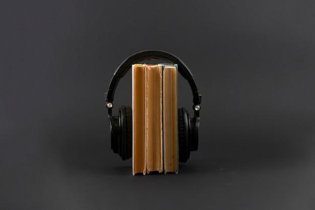 Das hörbuchkonzept anhören, große kopfhörer auf den bücherstapel legen, isoliert, einfacher stil