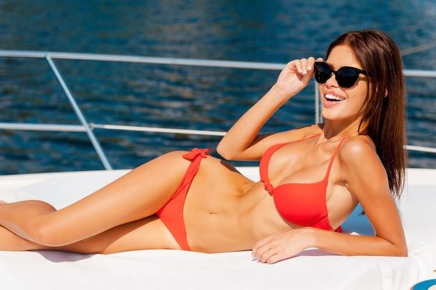 Das hohe leben leben. schöne junge frau im roten bikini, die brillen anpasst und in die kamera lächelt, während sie auf dem deck der yacht liegt?