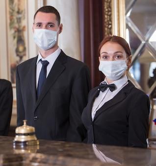 Das hotelpersonal serviert ihnen medizinische masken