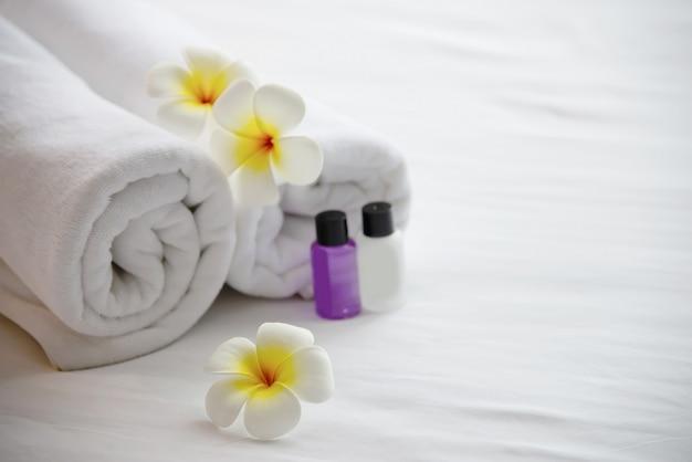 Das hoteltuch und die shampoo- und seifenbadflasche, die auf weißes bett mit der plumeriablume verziert wurden - entspannen sie sich ferien am hotelerholungsortkonzept