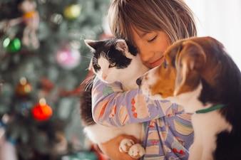 Das hübsche Mädchen, das Katze und Hund in Verbindung setzt