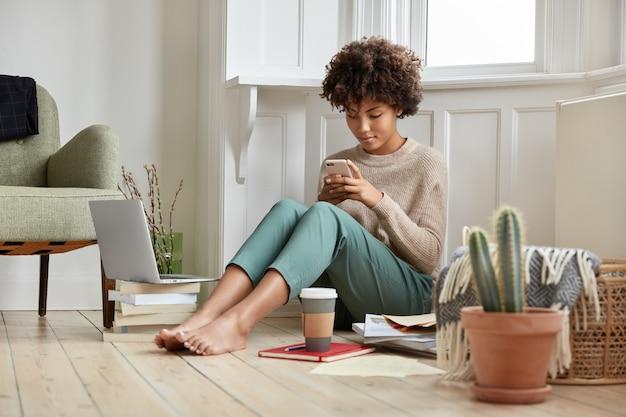 Das hübsche afro-mädchen sitzt in einem gemütlichen raum auf dem boden, durchsucht das profil in netzwerken, trinkt kaffee, arbeitet mit literatur und laptop, plaudert online auf dem handy, trägt einen lässigen pullover und eine hose