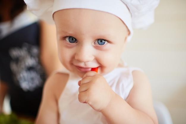 Das hübsche baby, das ein rotes papier isst