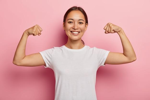 Das hübsche koreanische weibliche model hält sich fit und gesund, hebt die hände und zeigt muskeln, ist stolz auf ihre leistungen im fitnessstudio, lächelt breit, trägt weiße freizeitkleidung und zeigt indoor-shows mit echter kraft