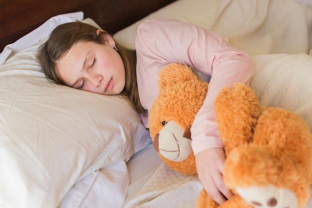 Das hübsche mädchen, das mit teddybären schläft, betreffen bett