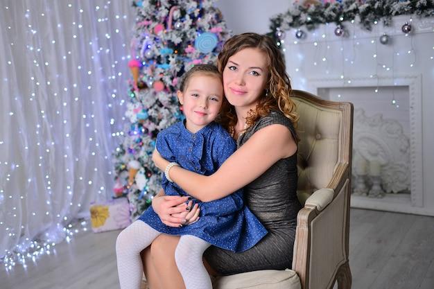Das hübsche mädchen mit mama schmücken einen weihnachtsbaum im haus