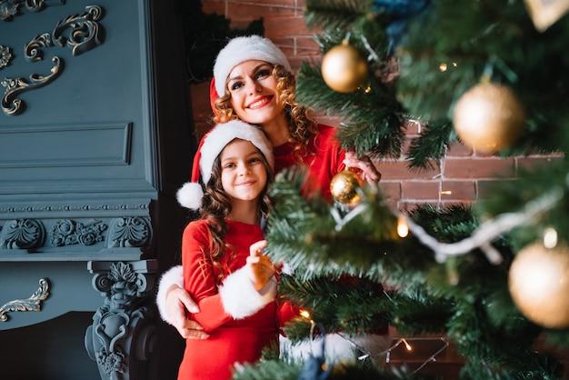 Das hübsche mädchen mit mama schmückt einen weihnachtsbaum im haus. glückliche familie.