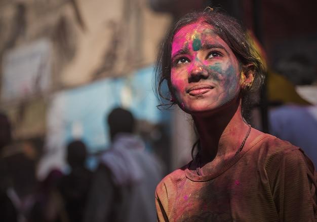 Das indische mädchen, das mit farben auf ihrem gesicht geschmiert wird, wirft während der holi festivalfeier auf