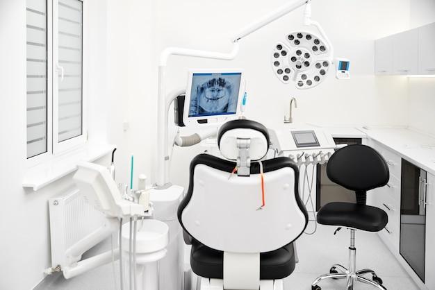 Das innere der klinik für stomatologie. zahnarztstuhl und werkzeuge mit röntgenbild im fernsehen im hintergrund. zahnpflege, zahnhygiene, checkup und therapiekonzept.