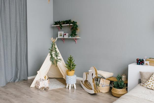 Das innere des kinderzimmers, dekoriert für weihnachten und neujahr. wigwam, schaukelpferd, weihnachtsbaum.