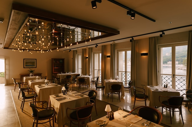 Das innere des restaurants besteht aus quadratischen tischen, stühlen und großen fenstern