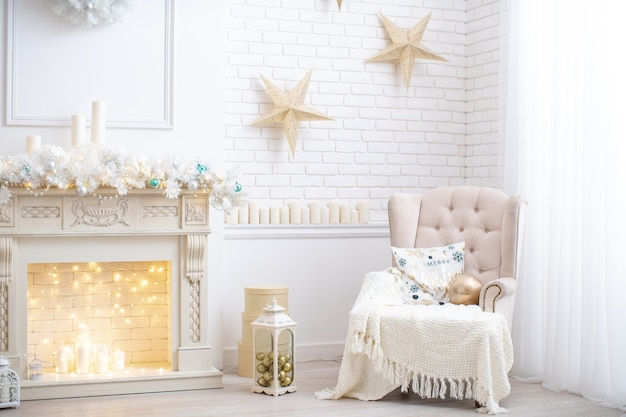 Das innere des wohnzimmers ist in hellen farben dekoriert und zu weihnachten dekoriert. neben dem kamin mit einer girlande geschmückt. sessel mit einer decke am fenster bedeckt