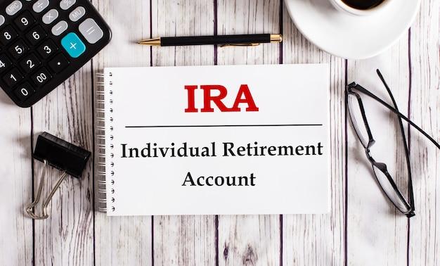 Das ira individual retirement account ist in einem weißen notizblock neben einem taschenrechner, kaffee, gläsern und einem stift geschrieben