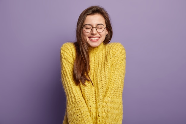 Das isolierte porträt einer glücklichen frau hat ein zahniges lächeln, schließt die augen, freut sich über ein gutes kompliment, trägt eine brille und einen gelben pullover und steht über einer lila wand. positives emotions- und gefühlskonzept