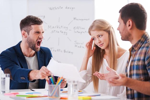Das ist alles falsch! zwei frustrierte geschäftsleute sitzen am tisch und gestikulieren, während ihr wütender chef papier hält und schreit