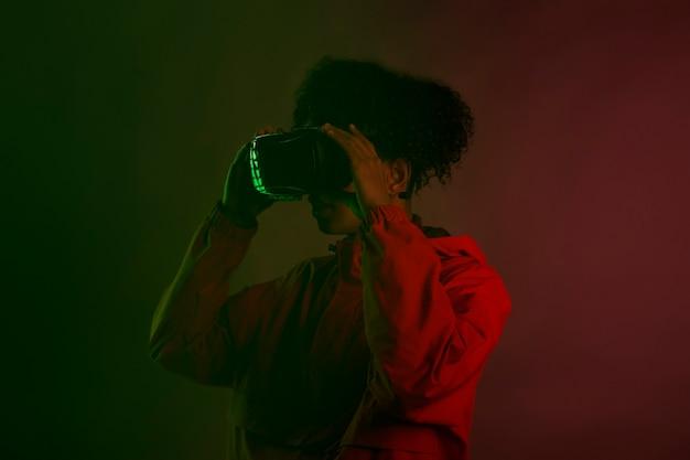 Das ist beeindruckend. afro junger mann, der virtual-reality-brille im dunklen raum mit neonlichtern trägt.