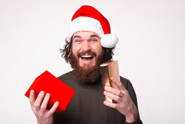 Das ist das geschenk, das ich wollte. überrascht bärtiger mann, der weihnachtshut trägt, hält eine geschenkbox.