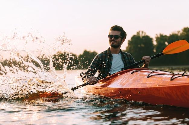 Das ist das wahre leben! hübscher junger lächelnder mann, der beim kajakfahren auf dem fluss wasser spritzt