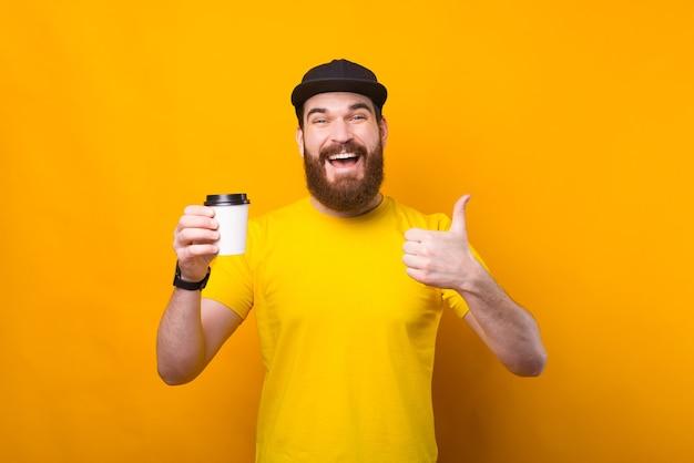 Das ist ein guter kaffee. glücklicher mann mit bart, der tasse kaffee hält und daumen oben zeigt