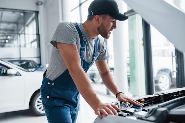 Das ist eine einfache aufgabe für diesen kerl. mann in blauer uniform und schwarzem hut, der beschädigtes automobil repariert