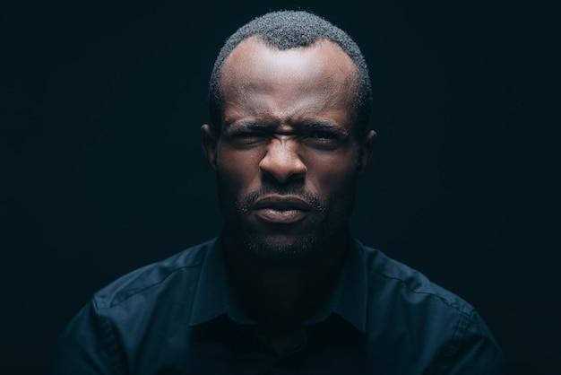 Das ist ekelhaft! porträt eines jungen afrikanischen mannes, der die kamera anschaut und ekel ausdrückt, während er vor schwarzem hintergrund ist