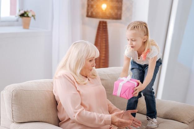Das ist für dich. nettes angenehmes positives mädchen, das ihre großmutter ansieht und eine geschenkbox hält, während sie ihr ein geschenk gibt