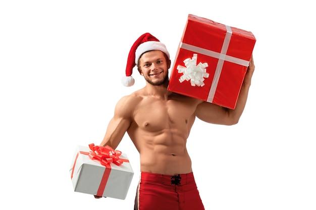 Das ist für dich. porträt eines nackten, zerrissenen mannes mit weihnachtsmann-hut, der ein geschenk hält und breit lächelt 2018, 2019.