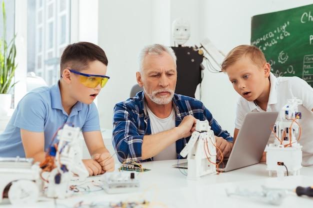 Das ist großartig. nette jungen, die auf den laptopbildschirm schauen, während sie ihre aufregung zeigen