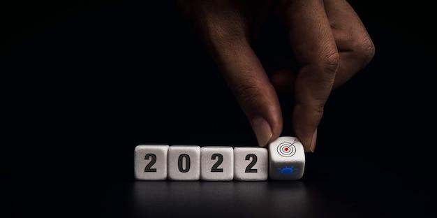 Das jahr 2021 wechselt auf 2022 mit dem ziel des covid-19-lagekonzepts. hand, die weiße würfelblöcke zum wechseln vom virussymbol zum zielsymbol auf dunklem hintergrund, modernem und minimalistischem stil umdreht.