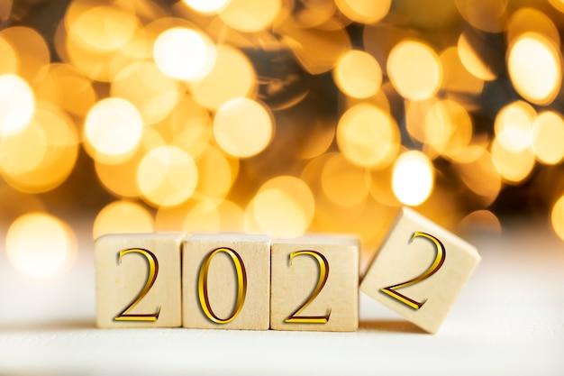 Das jahr 2022, geschrieben auf holzwürfeln in goldenen luxusbuchstaben mit glänzendem bokeh-hintergrund, neujahrsfeierkonzept glitzer