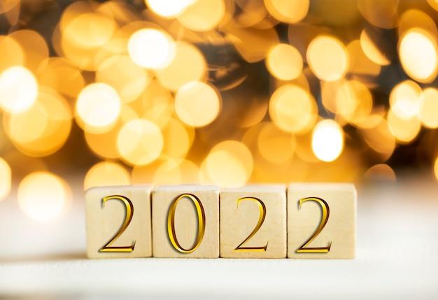Das jahr 2022, geschrieben auf holzwürfeln in goldenen luxusbuchstaben mit glänzendem bokeh-hintergrund, neujahrsfeierkonzept glitzerschönheit