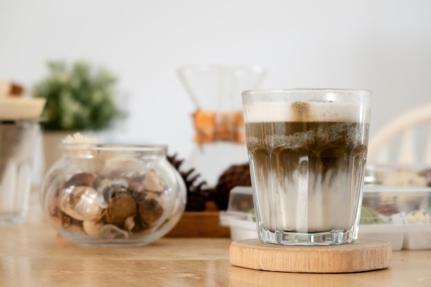 Das japanische hojicha-grüntee-getränk ist ein latte in einem glas auf einem holztablett.