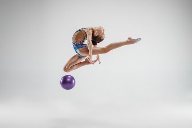 Das jugendlich weibliche kleine mädchen, das gymnastikübungen mit ball auf einem grauen studiohintergrund tut. das konzept gymnastik, stretch, fitness, lifestyle, training, sport