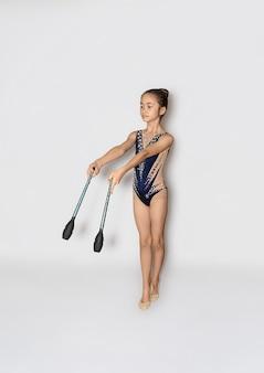 Das jugendlich weibliche kleine mädchen macht gymnastikübungen mit vereinen
