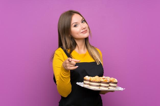 Das jugendlichmädchen, das viele verschiedene minikuchen über lokalisiertem purpurrotem hintergrund hält, zeigt finger auf sie