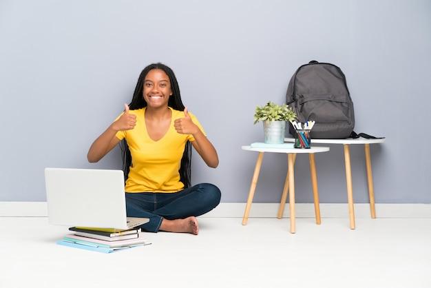 Das jugendlichstudentenmädchen, das auf dem boden gibt daumen sitzt, up geste