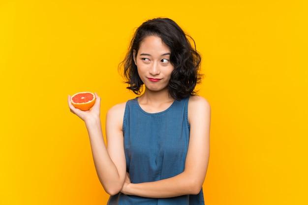 Das junge asiatische mädchen, das eine pampelmuse über lokalisierter orange wand macht zweifel hält, gestikulieren beim anheben der schultern