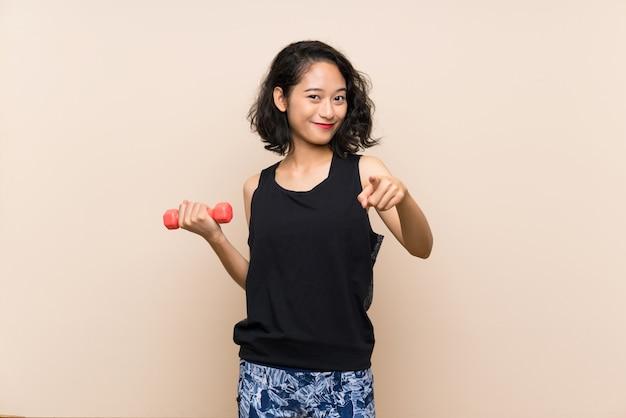 Das junge asiatische mädchen, das gewichtheben über lokalisiertem hintergrund macht, zeigt finger auf sie mit einem überzeugten ausdruck